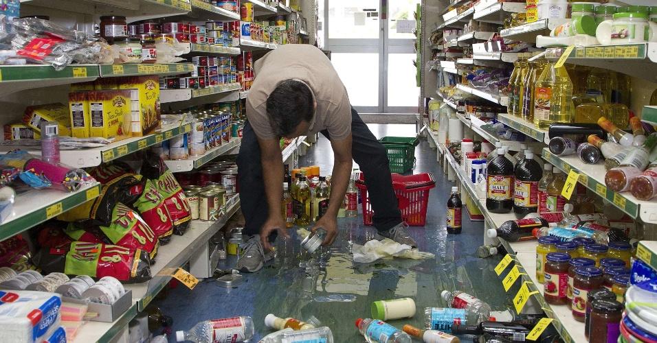 20.jan.2014 - Proprietário de mercado na pequena cidade neozelandesa de Eketahuna recolhe garrafas que foram ao chão por causa do terremoto de intensidade 6.3 que atingiu o norte do país nesta segunda-feira (20). O tremor interrompeu os serviços de trem, mas não há relatos de feridos