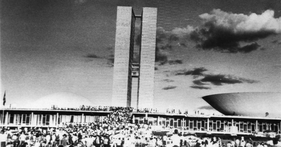 21.jan.2014 - Apesar de toda mobilização nacional, a emenda constitucional Dante de Oliveira não foi aprovada pelo congresso. No dia da votação, em 25 de abril de 1984, 113 deputados (todos do PDS) não foram ao plenário e a emenda acabou sendo rejeitada. Ela obteve 298 votos favoráveis e 65 contrários, além de três abstenções. Mas, eram precisos mais 22 votos a favor para a aprovação. Na foto, de pessoas protestam em frente ao congresso, em Brasília, contra a rejeição da medida