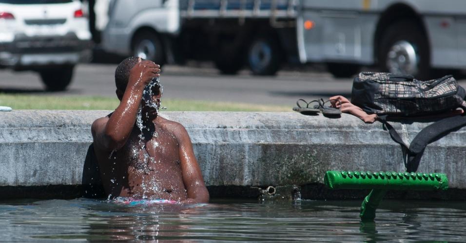 22.jan.2014 - Homem se banha no chafariz da Candelária, no Centro do Rio, para escapar da sensação térmica de mais de 40 graus da cidade, nesta quarta feira (22)