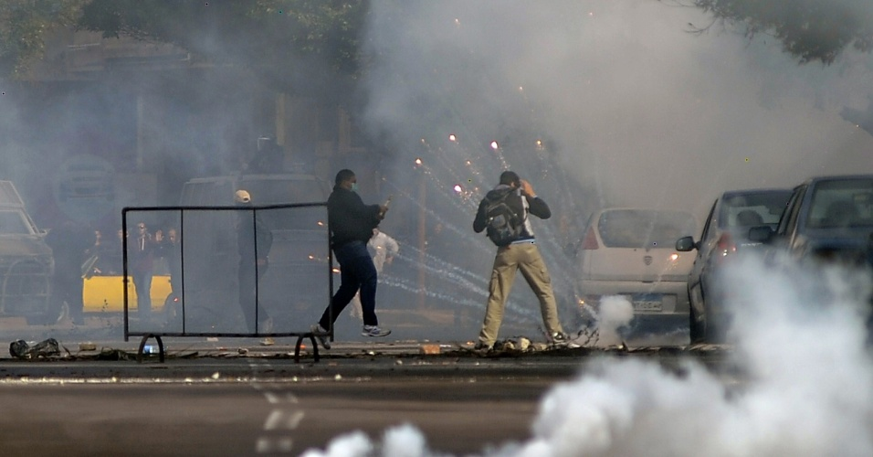 23.jan.2014 - Manifestantes egípcios e apoiadores da Irmandade Muçulmana se espalham enquanto bombas de gás explodem próximas a eles, durante confrontos com a polícia no norte da cidade de Alexandria, no Egito, nesta quinta-feira (23). Conflitos entre estudantes egípcios rivais de uma universidade em Alexandria mataram ao menos uma pessoas, que apoiava o ex-presidente egípcio deposto, Mohammed Mursi