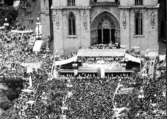 """23.jan.2014 - O ato público foi coordenado por uma frente única, milhares de pessoas encheram a praça da Sé, onde permaneceram 12 horas, apesar da chuva. Foi a primeira das manifestações gigantes que nos três meses seguintes agitariam o país. No palanque, políticos de todos os partidos eram aplaudidos ao lado de sindicalistas, estudantes, intelectuais e artistas. A dinâmica era a mesma do comício de duas semanas antes em Curitiba, que serviu de ensaio para o ato de São Paulo. Hinos, discursos contra o governo e muita camiseta amarela com os dizeres """"Eu Quero Votar Pra Presidente"""""""