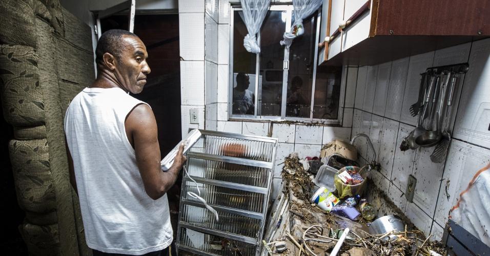 23.jan.2014 - O manobrista Valdi Paulo da Silva, 48 , mostra os estragos causados pelo temporal que atingiu a região de Taboão da Serra. A chuva forte que atingiu São Paulo, entre a tarde e a noite de quarta-feira (22), provocou estragos na zona sul da capital e na Grande São Paulo. Os transbordamentos de um piscinão e de córregos alagaram ruas, casas e provocaram os desabamentos de muros e lajes de casas. Não há informações de vítimas
