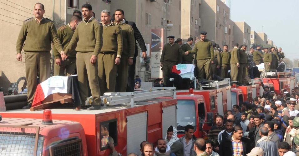 23.jan.2014 - Policiais se aglomeram ao redor de caixões durante o funeral dos cinco policiais mortos quando homens mascarados motorizados abriram fogo em um ponto de inspeção na província de Beni Suef, a 100 km ao sul do Cairo, no Egito, nesta quinta-feira (23)