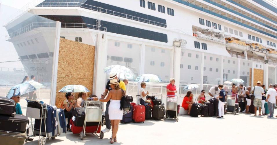 26.jan.2014 - Passageiros aguardam transatlânticos com guarda-sóis temáticos na praça Mauá, Rio de Janeiro