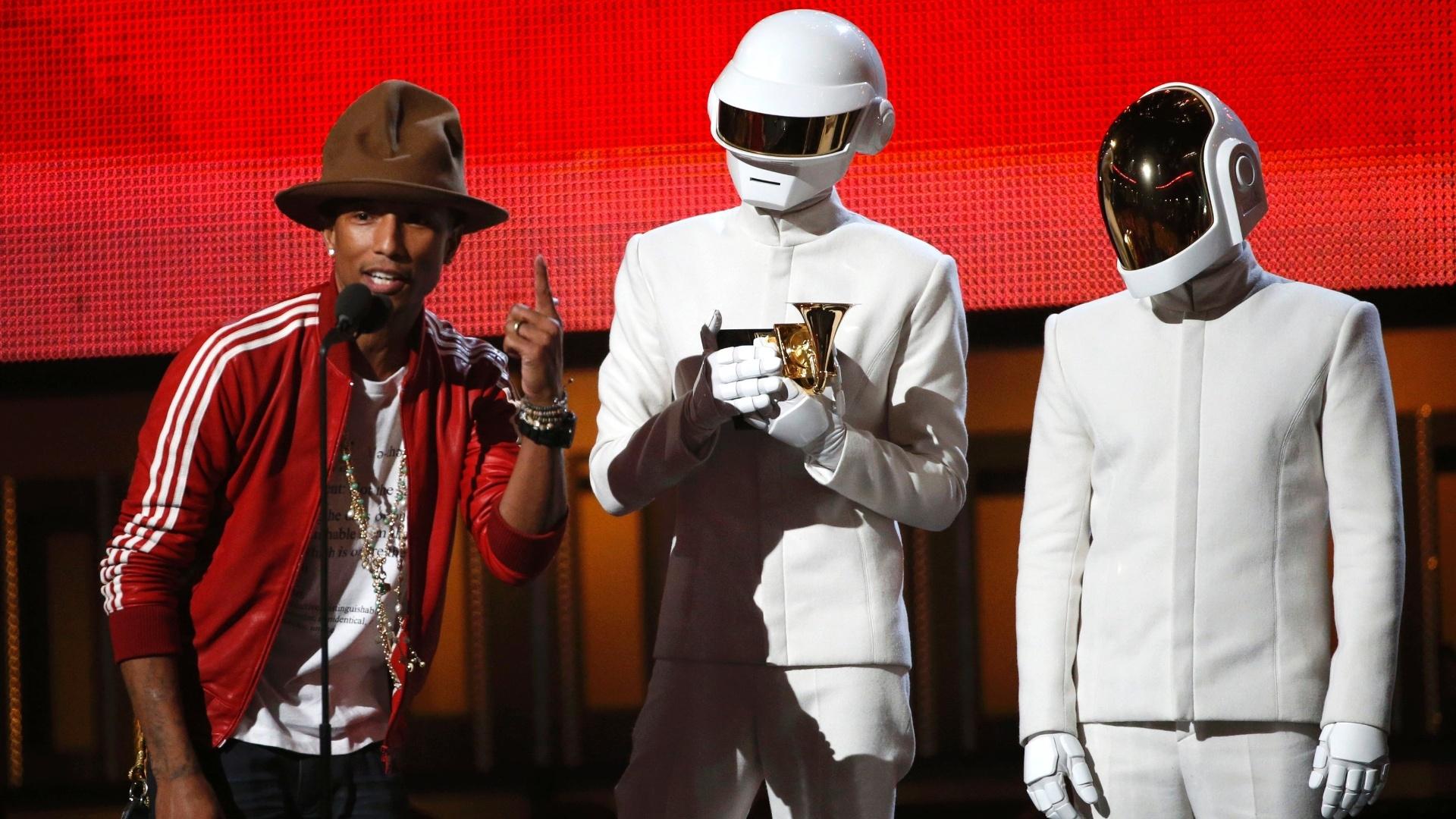 27.jan.2014 - A dupla de música eletrônica Daft Punk (com capacetes), acompanhada do cantor Pharrell Williams, recebe o troféu de melhor álbum do ano na festa do Grammy 2014, realizada nesta segunda-feira (27) em Los Angeles (EUA). O Daft Punk saiu do evento como maior vencedor, recebendo cinco