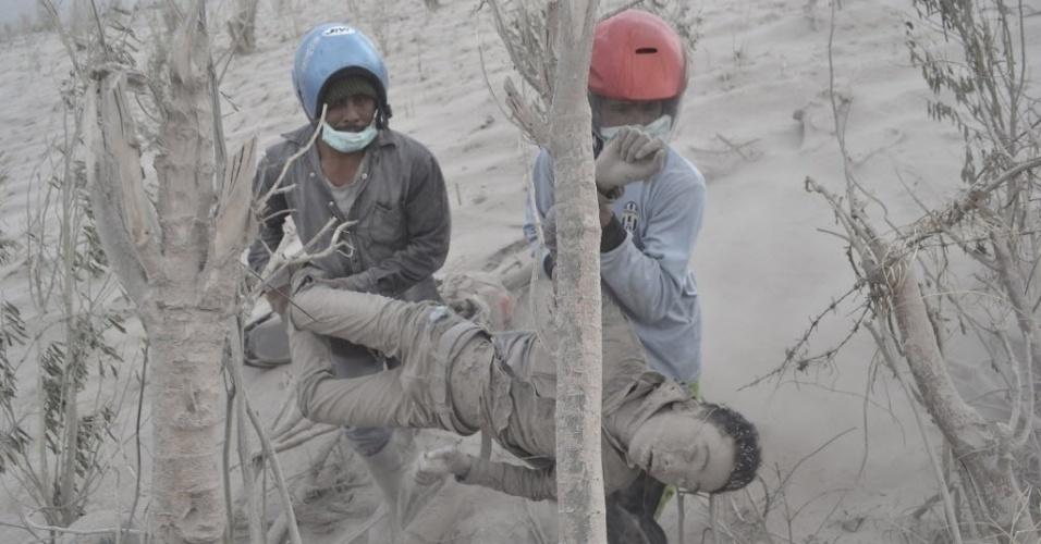 1.fev.2014 - Dois homens carregam vítima de lava vinda do Monte Sinabung no vilarejo de Suka Meriah, na Indonésia. A erupção do vulcão matou 11 pessoas neste sábado (1), do lado ocidental da ilha de Sumatra