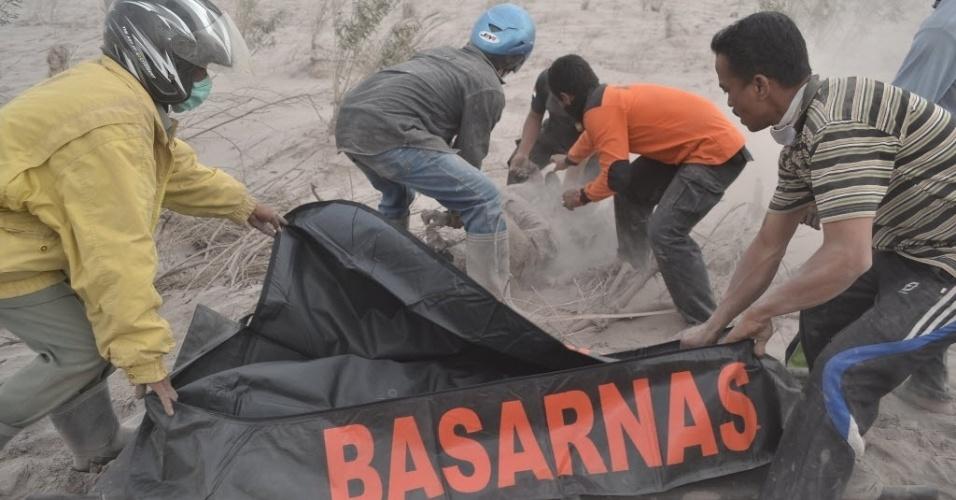 1.fev.2014 - Homens resgatam corpo de uma vítima da erupção do Monte Sinabung, localizado na ilha de Sumatra, na Indonésia. Ao menos 11 pessoas morreram, envolvidas pelas cinzas do vulcão