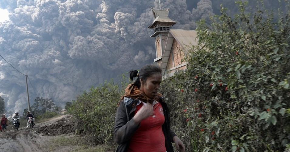 1.fev.2014 - Mulher foge enquanto o Monte Sinabung entra em erupção próximo à vila de Bekerah, no distrito de Karo, na ilha de Sumatra, que fica no oeste da Indonésia. Ao menos 11 pessoas morreram com a erupção do vulcão, que ficou dormente por 400 anos até voltar à atividade em 2010