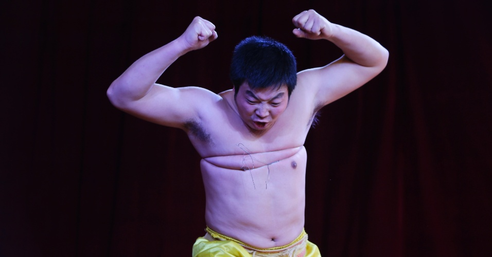 2.fev.2014 - Chinês tenta quebrar fio de ferro amarrado em volta de seu peito enquanto executa Qigong, uma forma tradicional de arte  marcial chinesa, durante celebração do terceiro dia do Ano-Novo Lunar chinês no parque Daguanyuan, em Pequim (China)