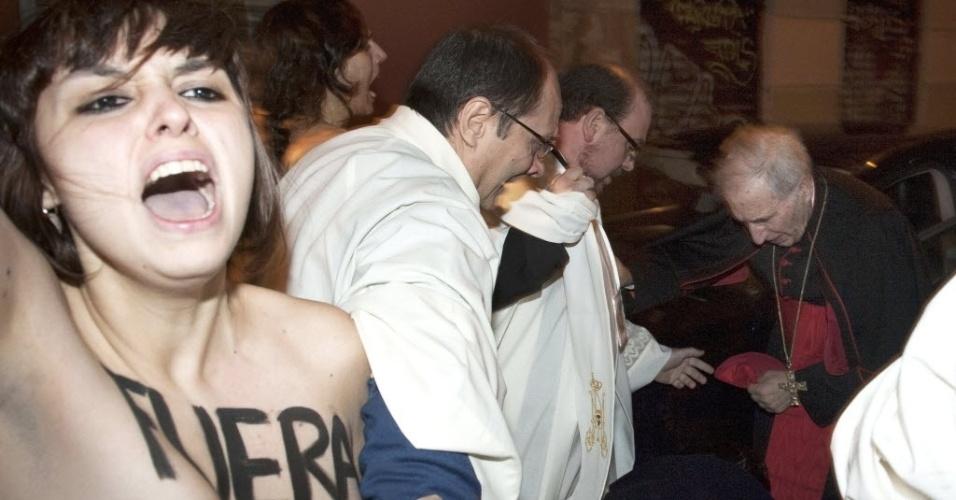 """2.fev.2014 - Cinco ativistas do Femen, sem camisa e gritando """"o aborto é sagrado"""", abordam o Cardeal Arcebispo de Madri, António Maria Rouco Varela (à dir.), enquanto ele se preparava para entrar na paróquia dos Santos Justo e Pastor"""