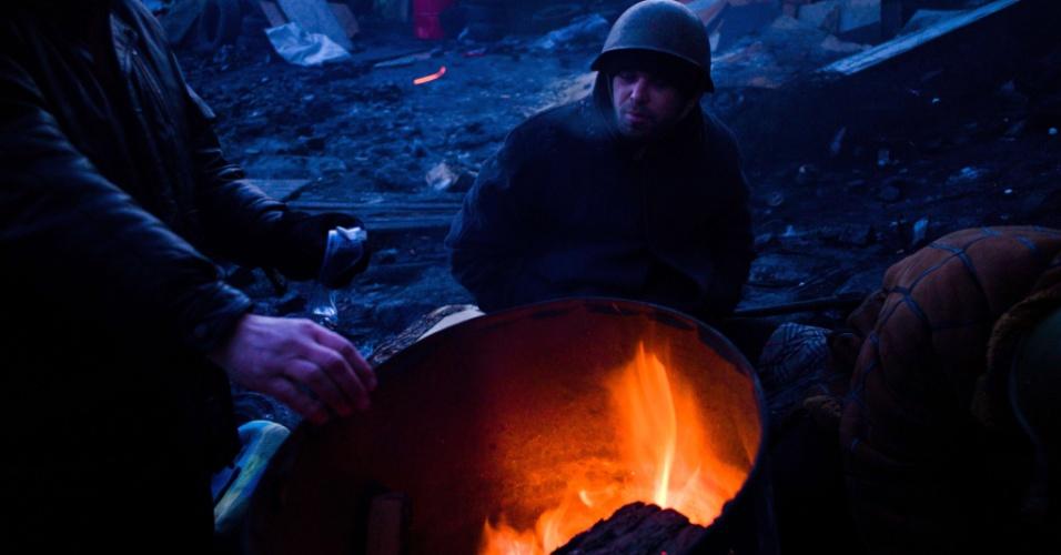 2.fev.2014 - Manifestantes contrários ao governo ucraniano se esquentam em fogueira feita em barricada na manhã deste domingo (2) em Kiev. Segundo a oposição, as autoridades ucranianas estão considerando a possibilidade de instaurar o estado de exceção no país para acabar com mais de dois meses de protestos