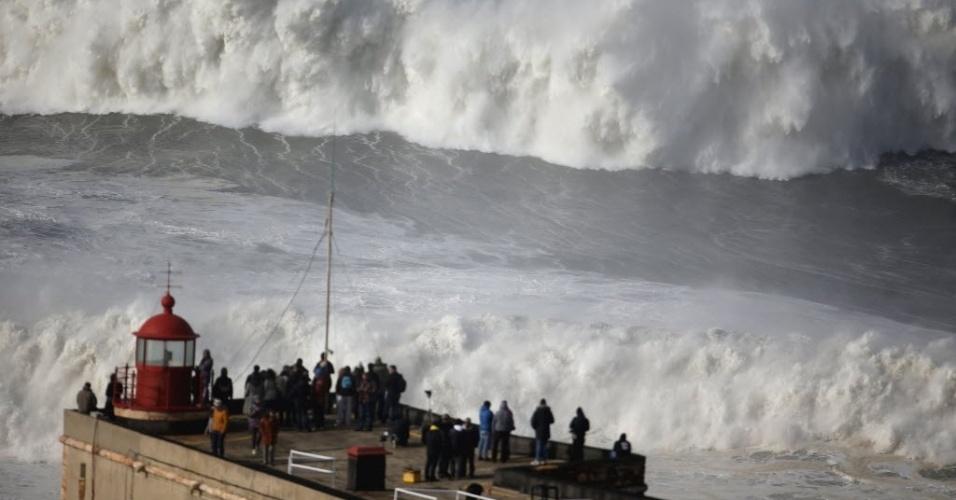 2.fev.2014 - Pessoas assistem às fortes ondas de um farol em Nazaré. Um alerta laranja para o mau tempo continua em vigor para toda a costa de Portugal