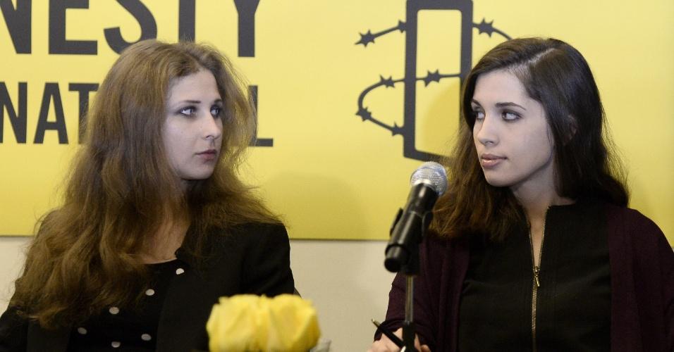 4.fev.2014 - Ativistas russas do grupo Pussy Riot Maria Alyokhina (esq.) e Nadezhda Tolokonnikova (dir.) falam com imprensa no escritório da Anistia Internacional, em Nova York, nesta terça-feira (4). Elas participaram de um show voltado para a luta pelos direitos humanos na cidade