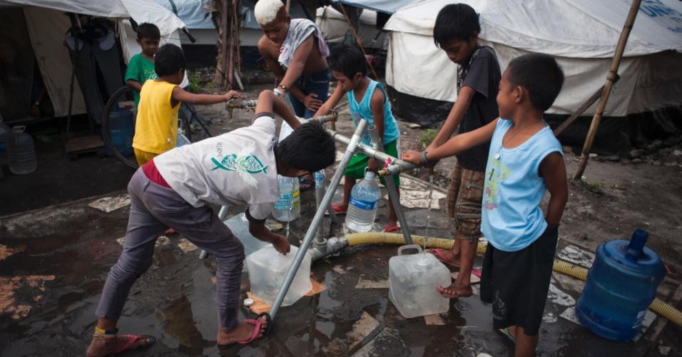 4.fev.2014 - Crianças recolhem água de um bebedouro improvisado criado pela ONU em Tacloban, nas Filipinas. Quase três meses após o tufão Haiyan, a universitária e capital da província, que era próspera, apresenta poucos sinais de recuperação econômica