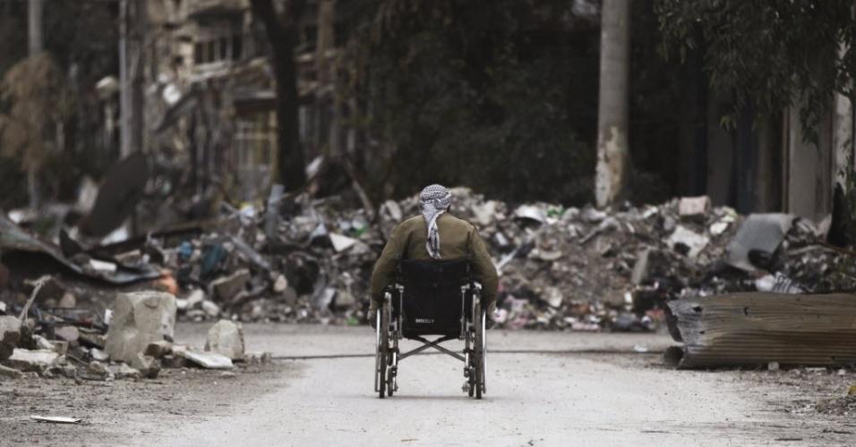 4.fev.2014 - Homem em cadeira de rodas anda por rua coberta de destroços em Deir al-Zor, no leste da Síria