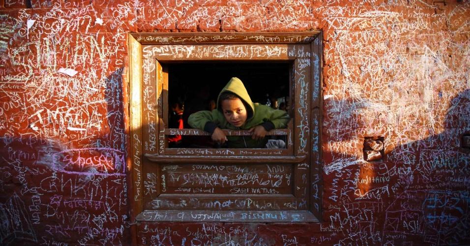 4.fev.2014 - Menino olha pela janela do templo Saraswati, cujas paredes estão cheias de escritos, durante o festival Shreepanchami, em Kathmandu, Nepal, nesta terça-feira (4)
