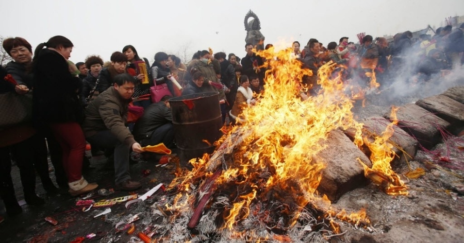 4.fev.2014 - Pessoas queimam incenso em homenagem ao deus da fortuna durante o quinto dia do Ano-Novo Lunar Chinês, no templo budista de Guiyuan, na província chinesa de Hubei