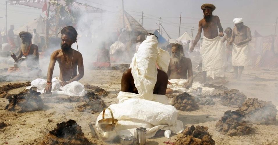 4.fev.2014 - Sadhus, homens hindus sagrados, fazem preces enquanto sentam dentro de círculos de upale, fezes de vaca secas, que são queimadas às margens do rio Ganges durante o festival Magh Mela, na cidade de Allahabad, na Índia