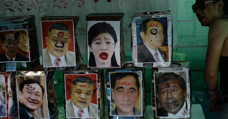 4.fev.2014 - Um manifestante tailandês anti-governo observa fotos que ironizam a primeira-ministra do país Yingluck Shinawatra, seu irmão, o ex-primeiro ministro Thaksin Shinawatra e outros ministros do governo. As fotos foram colocadas em blocos empilhados para serem derrubados por bolas de tênis, durante um protesto no centro de Bancoc, nesta terça-feira (4). A oposição, que boicotou as eleições antecipadas de domingo passado (2), apresentou nesta terça-feira (4) um recurso na Corte Constitucional do país pedindo a anulação do pleito