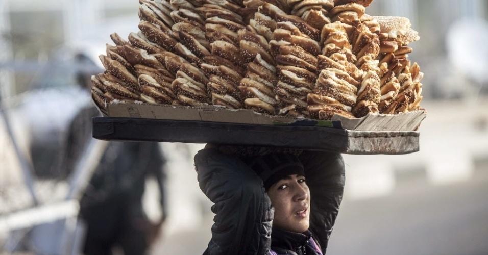 4.fev.2014 - Vendedora carrega bandeja com doces em frente à Academia de Polícia do Cairo, no Egito, onde acontece nesta terça-feira (4) uma nova audiência sobre a acusação de assassinato enfrentada pelo presidente deposto do Egito, Mohamed Mursi. Junto com 14 pessoas, Mursi é acusado de incitar o assassinato de ativistas que protestavam do lado de fora do palácio presidencial egípcio em dezembro de 2012