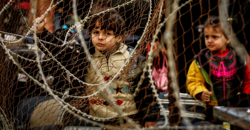 5.fev.2014 - Criança palestina espera com sua família para entrar a Egito através da passagem fronteiriça de Rafah, na Faixa de Gaza. O país reabriu o caminho na terça-feira (4), depois de manter o portão principal do enclave palestino fechado para o mundo exterior por 12 dias