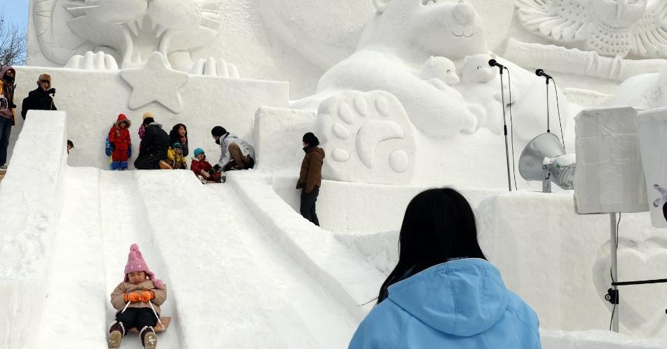 5.fev.2014 - Crianças brincam em tobogã de neve durante o 65º festival anual de Sapporo, no Japão, nesta quarta-feira (5). O evento de uma semana começou com um total de 198 esculturas de neve em exposição