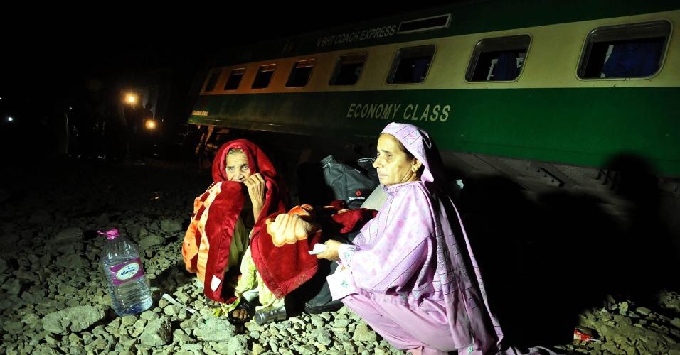 5.fev.2014 - Passageiras aguardam socorristas no local onde uma bomba explodiu na via férrea nos arredores de Karachi (Paquistão), nesta quarta-feira (5). Pelo menos três passageiros, incluindo uma criança, morreram no atentando