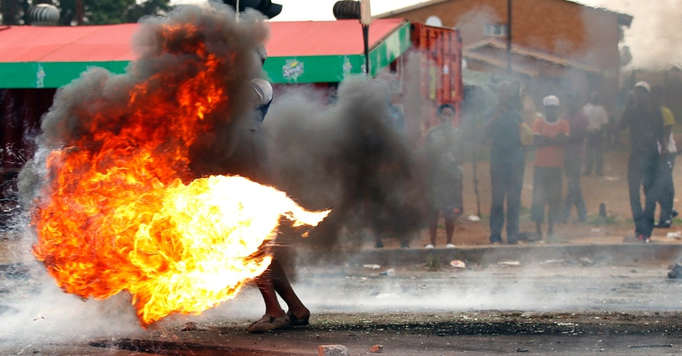 5.fev.2014 - Sul-africano manuseia pneu em chamas durante protesto na cidade de Sebokeng contra a má prestação de serviços públicos