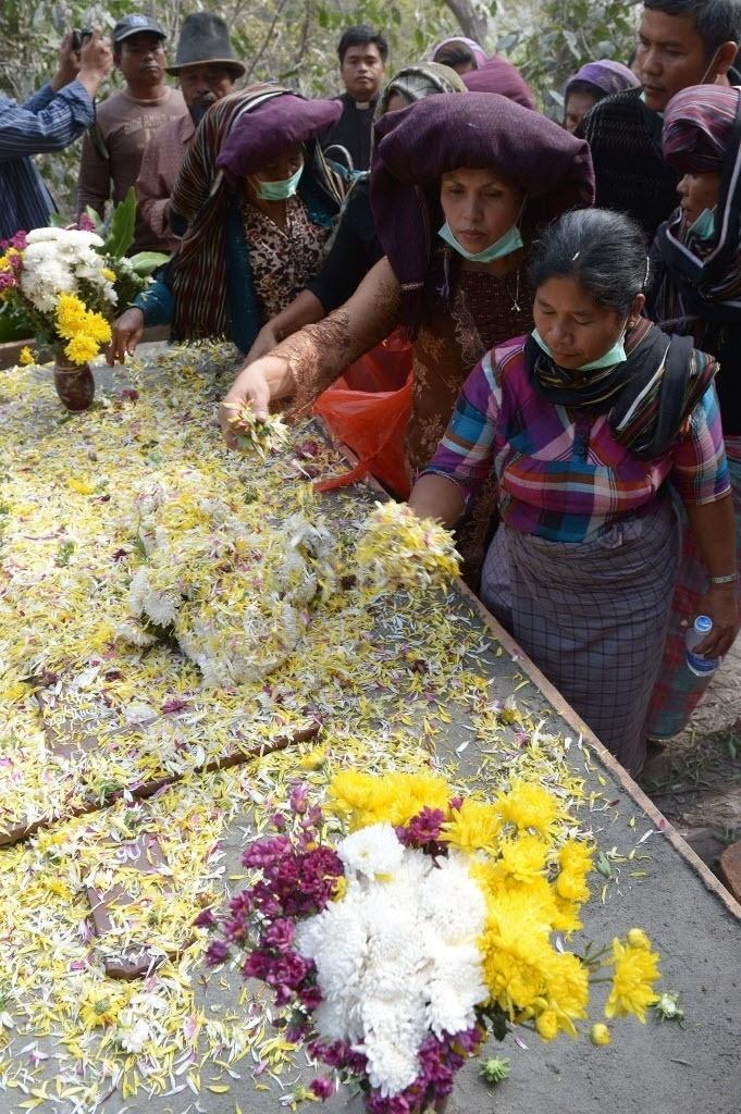 6.fev.2014 - Familiares jogam flores no túmulo de Doni Meliala, uma das vítimas da erupção do vulcão Monte Sinabung na vila de Gurki Nayan, na Indonésia. No último sábado (1) uma erupção do vulcão, que vem expelindo cinzas e lava desde setembro do ano passado, causou a morte de 15 pessoas