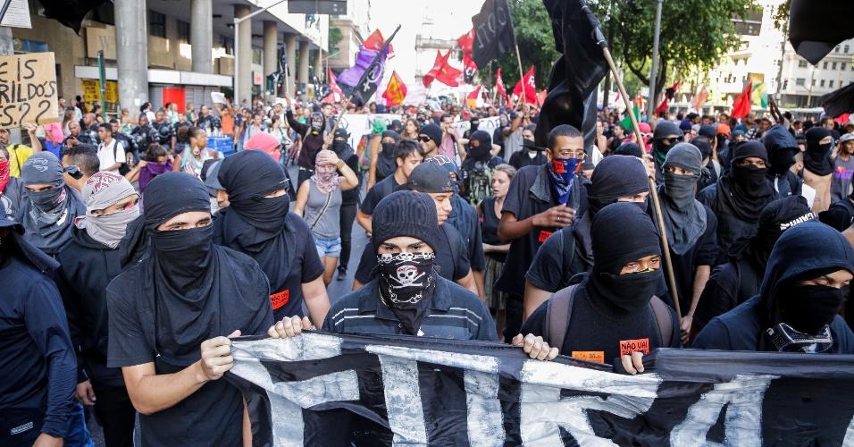 6.fev.2014 - Manifestantes mascarados seguram faixas durante ato contra o aumento das passagens de ônibus, que teve concentração na região da Candelária, no centro do Rio de Janeiro, nesta quinta-feira (6)