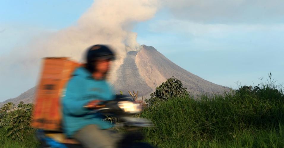 6.fev.2014 - Motociclista passa em estrada com o vulcão Sinabung ao fundo, expelindo fumaça e cinzas quentes, em Karo (Indonésia), nesta quinta-feira (6). O monte, que matou 15 pessoas no último fim de semana, passou por mais uma erupção, atirando cinzas quentes e rochas para o alto novamente em 3 de fevereiro, interrompendo uma busca por mais vítimas