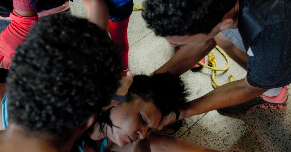 6.fev.2014 - Mulher desmaia durante confronto com policiais militares em protesto contra aumento da tarifa de ônibus, na Central do Brasil, centro do Rio de Janeiro