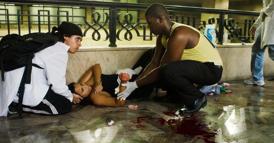 6.fev.2014 - Mulher ferida é amparada por manifestantes durante confronto com policiais militares após protesto contra aumento da tarifa de ônibus, na Central do Brasil, centro do Rio de Janeiro