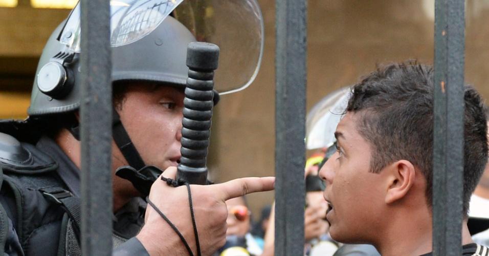 6.fev.2014 - Policial encara manifestante durante protesto contra aumento da tarifa de ônibus, nesta quinta-feira (6), na Central do Brasil, no Rio de Janeiro
