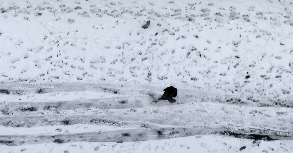 Homem caminha entre rua coberta de neve em Tóquio (Japão). A Agência Meteorológica do país disse que o acúmulo de neve chegou a 27 centímetros após a nevasca mais pesada desde fevereiro de 1994 atingir a capital japonesa. Foi a quarta maior queda de neve desde a Segunda Guerra Mundial, e a agência emitiu seu primeiro aviso forte de nevasca para o centro de Tóquio em 13 anos