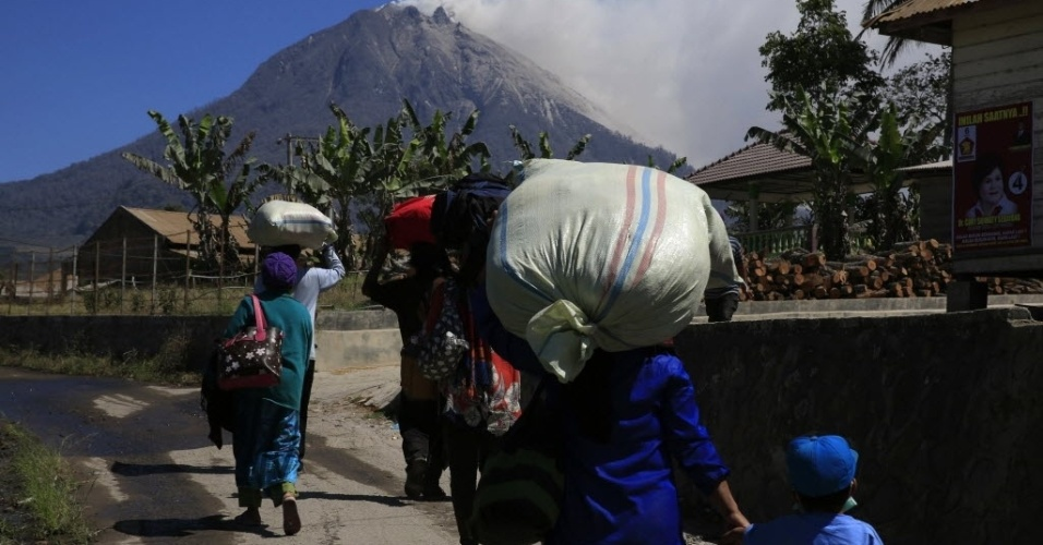 10.fev.2014 - Moradores da vila de Rimo Kayu, na Indonésia, carregam pertences enquanto voltam para suas casas, após viverem por dois meses em um abrigo temporário, por conta das constantes erupções do vulcão Monte Sinabung. o Centro de Vulcanologia e Redução de Ameaças Geológicas expediu uma recomendação para que as pessoas permaneçam a uma distância mínima de 5 km do vulcão. A vila de Rimo Kayu fica a 7 km do vulcão