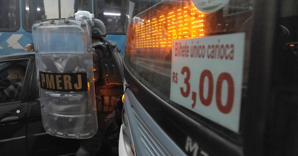 10.fev.2014 - Policial militar transita entre os veículos durante protesto contra aumento das passagens de ônibus, no centro do Rio de Janeiro, nesta segunda-feira (10)