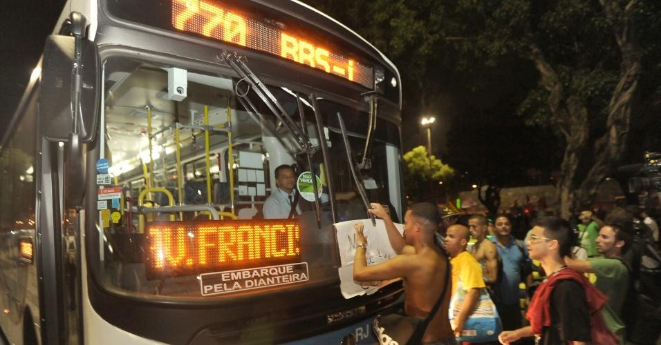 13.fev.2014 - Manifestantes colocam cartaz em para-brisa de ônibus durante protestocontra o aumento da passagem de ônibus no centro do Rio de Janeiro, nesta quinta-feira (13). Pelo menos mil pessoas participam do ato, que segue pacífico