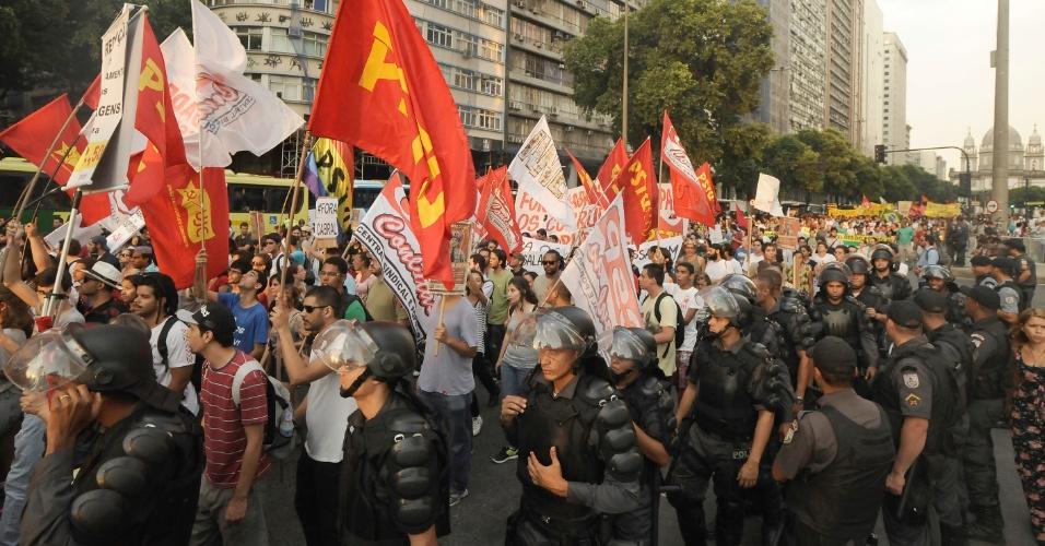 13.fev.2014 - Policiais acompanham cerca de mil manifestantes que saíram em passeata pelo centro do Rio de Janeiro em um novo protesto contra o aumento da tarifa de ônibus na cidade
