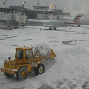 13.fev.2014 - Escavadeira retira neve das áreas de porta avião no aeroporto de La Guardia, em Nova York