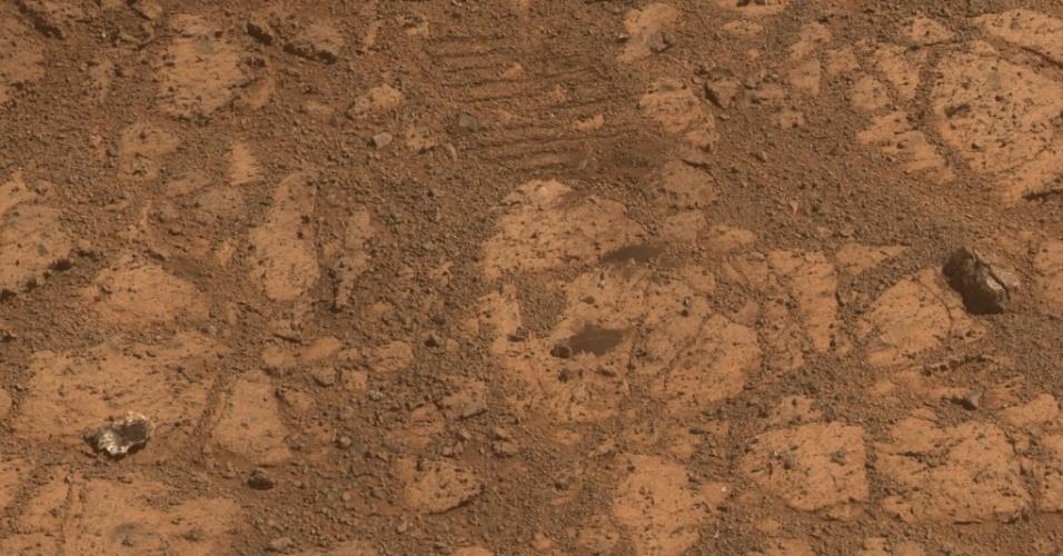 """14.fev.2014 - MEIO DO CAMINHO, TINHA UM DONUT - No canto esquerdo da parte de baixo desta foto, há uma pedra. Mas não uma pedra comum. Ela é responsável por um enigma que intrigou a Nasa: o """"mistério do donut marciano"""". No começo de janeiro deste ano, um pedaço de pedra em forma de donut apareceu repentinamente na frente da sonda terrestre Curiosity, sem nenhuma explicação. Mas os cientistas agora descobriram que o """"donut"""" era apenas uma parte dessa pedra que você vê aí em cima. Solução do mistéro: robô da Nasa tinha atropeado a pedra e arrancou dela um pedaço em forma de donut"""