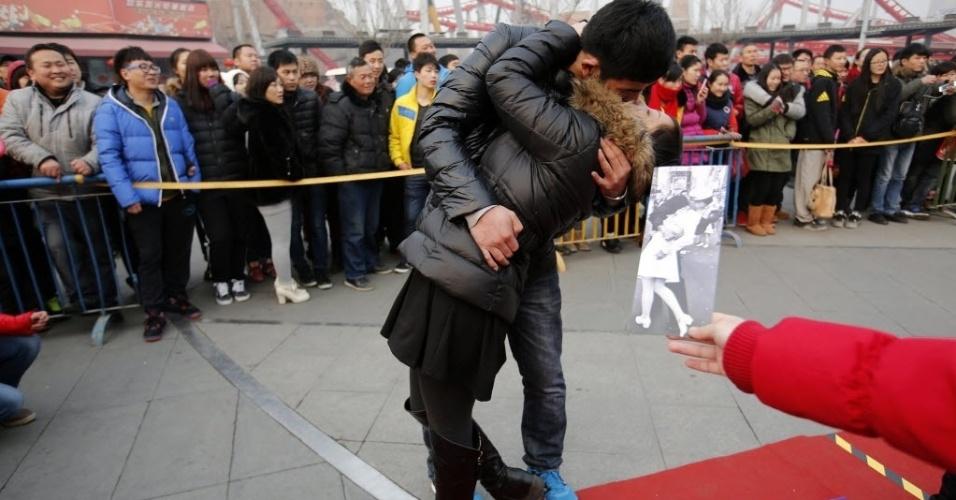14.fev.2014 - Juiz segura foto de beijo famoso que casal deve imitar durante concurso de beijos em parque de diversões em Pequim, na China. Cerca de cem casais participaram da competição, organizada em comemoração ao Valentine's Day (Dia dos Namorados) e cujo prêmio era um iPhone 5S
