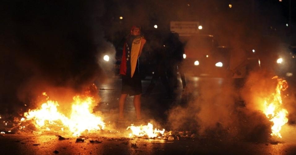 14.fev.2014 - Manifestante participa de bloqueio em estrada em Caracas, na Venezuela, em protesto contra o governo de Nicolas Maduro, na noite desta quinta-feira (13). A corte venezuelana ordenou a prisão do líder da oposição Leopoldo Lopez, sob acusação de assassinato e terrorismo. As acusações são ligadas aos protestos que resultaram na morte de três pessoas na última quarta-feira (12)
