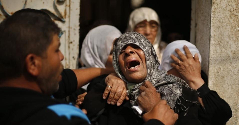 14.fev.2014 - Mãe de jovem palestino morto por soldados israelenses chora durante funeral em Gaza, nesta sexta-feira (14). Familiares do jovem disseram que ele recolhia gravetos para vender em uma carroça quando foi morto pelos soldados. Militares israelenses disseram que os soldados atiraram em palestinos que tentavam passar ilegalmente por uma bairreira de segurança