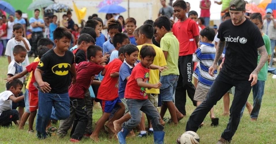 14.fev.2014 - O britânico David Beckham joga futebol com crianças filipinas em uma escola de Tanuan, na região central do país. É o segundo dia da visita de Beckham às Filipinas, para onde viajou para dar apoio aos sobreviventes do tufão Haiyan