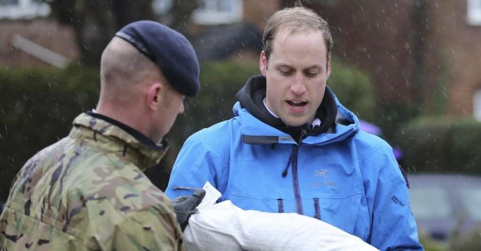 14.fev.2014 - O príncipe William ajuda militares a carregar sacos de areia em Datchet, no centro da Inglaterra, nesta sexta-feira (14), como parte dos esforços para conter as inundações históricas que atingem o país. O príncipe Harry também participou da ação na localidade atingida pela inundação do Rio Tâmisa