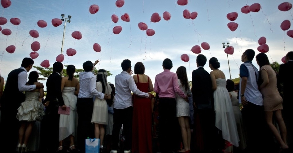 14.fev.2014 - Recém-casados soltam balões em formato de coração durante cerimônia de casamento coletivo realizada em templo em Kuala Lumpur, na Malásia. Cerca de 138 casais escolheram celebrar sua união nesta sexta-feira (14) por ser o dia de São Valentim, considerado o dia dos namorados em boa parte do mundo.