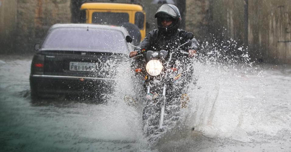 15.fev.14 - Motoqueiro atravessa ponto de alagamento na passagem que dá acesso do Parque Ecologico do Tietê a Avenida Assis Ribeiro, na zona leste de São Paulo (SP), neste sábado (15). Cidade enfreta fortes chuvas desde a manhã
