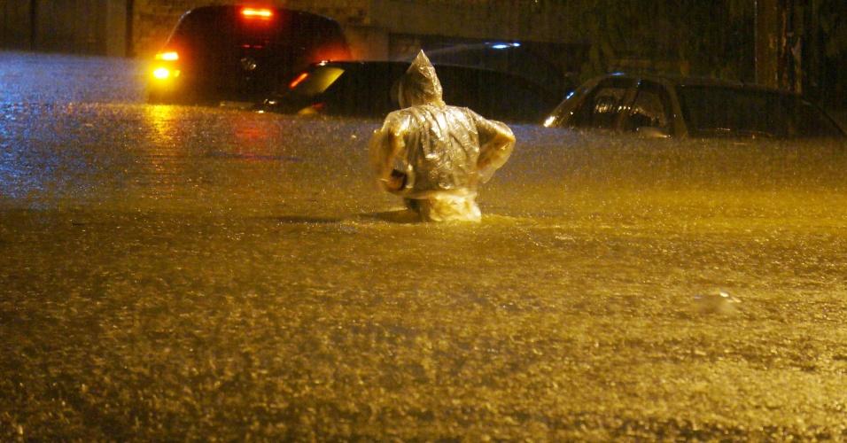 15.fev.2014 - Homem caminha pela rua Venâncio Aires, com a avenida Pompeia, na zona oeste de São Paulo, alagada depois que forte chuva atingiu a cidade na noite de sexta-feira (14)