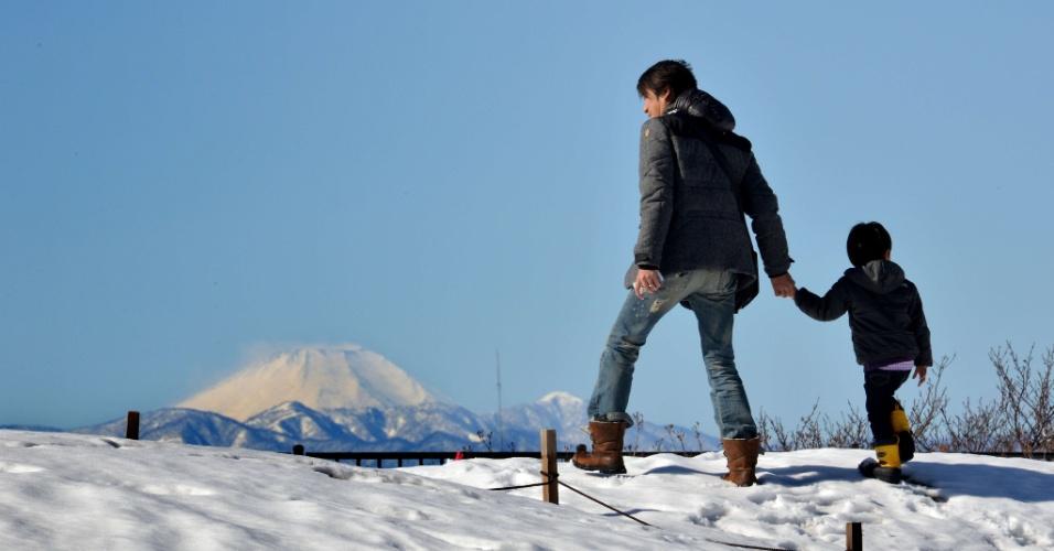16.fev.2014 - Menino e seu pai andam em campo coberto de neve, com o Monte Fuji ao fundo, em Tóquio, no Japão